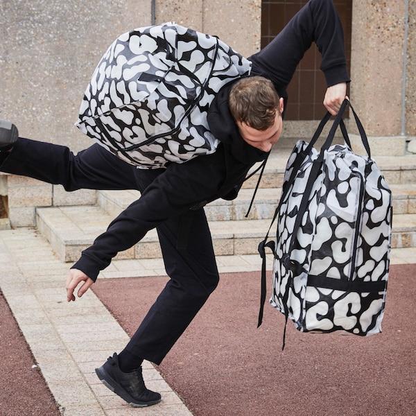 一位男子肩上背着一个 OMBYTE 欧姆比特 黑色透明袋,手上还拎着一个,正在尝试跳出舞步。