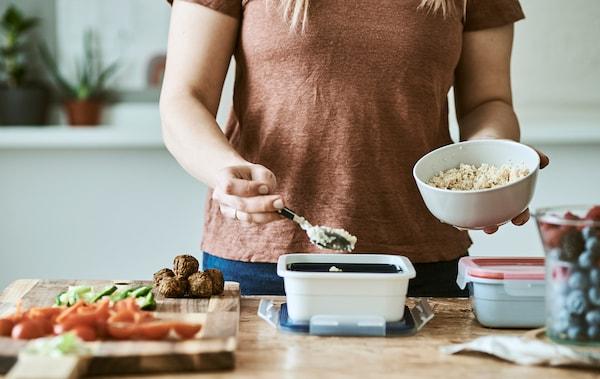 一位女士把蒸粗麦粉从一只白色碗里舀到一只塑料食盒中。在木桌上有一块砧板,上面有切好的蔬菜。