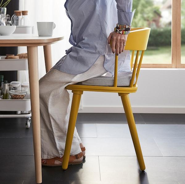 一位女士扶着高高的椅背,从 OMTÄNKSAM 沃姆安克萨姆 椅子上站了起来。圆形的椅背和座椅可以提高舒适感。
