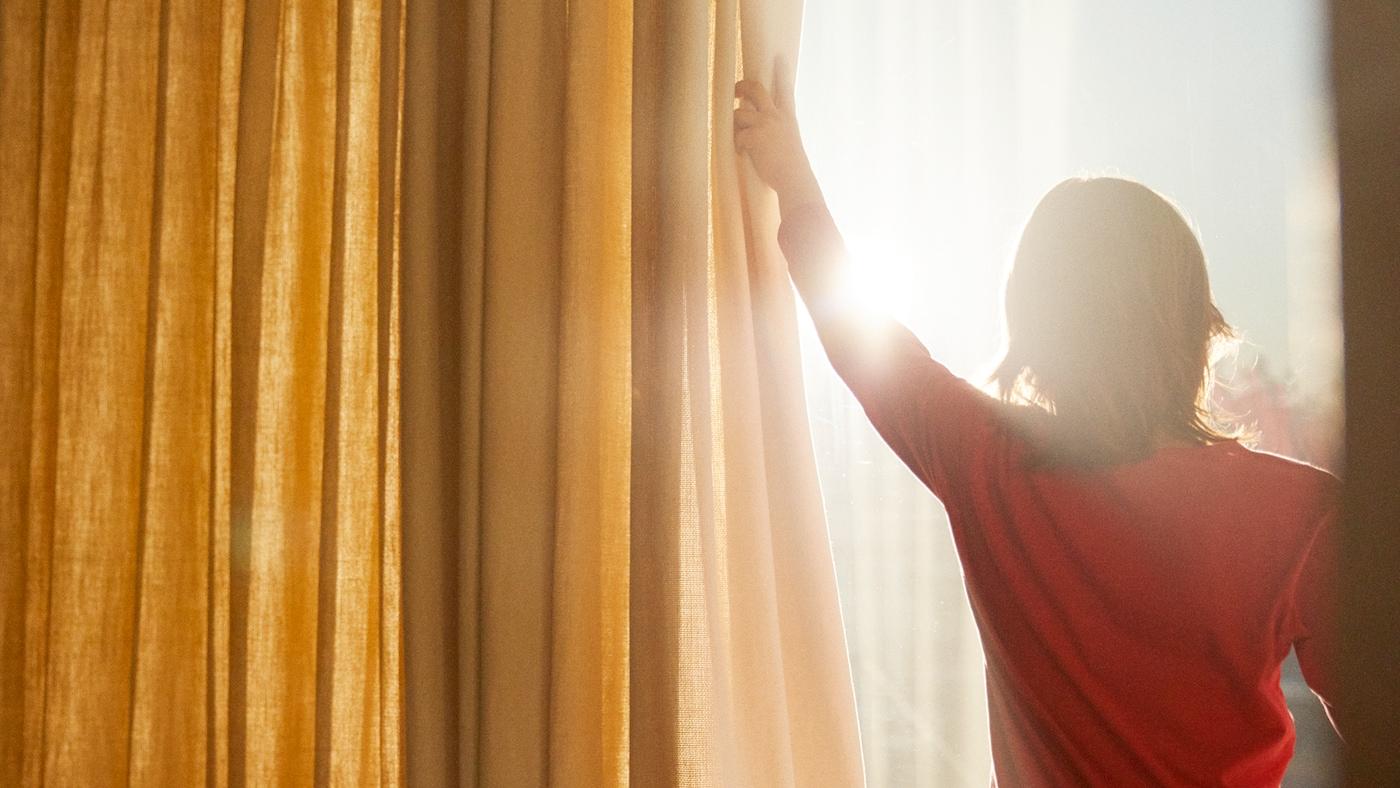 一位女士拉开窗帘沐浴阳光。