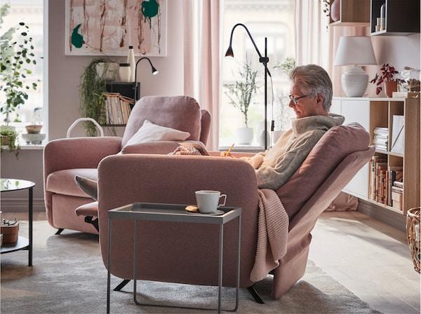 一位女士惬意地坐在茶几旁带 GUNNARED 刚纳瑞德 浅棕粉色垫套的 EKOLSUND 艾克桑 躺椅上。