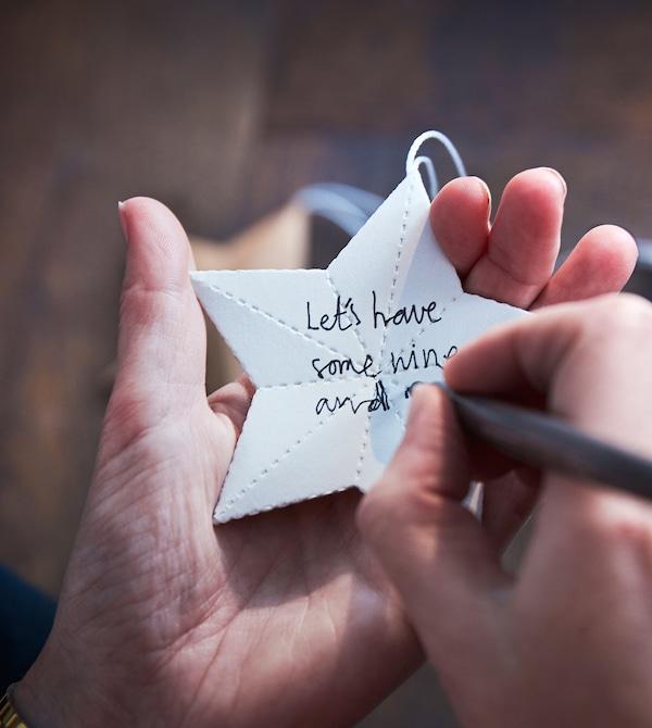 一位女士在纸星星上写下节日愿望。