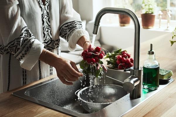 一位女士站在水槽边,开着 ÄLMAREN 艾玛兰 厨房水龙头,正在冲洗一把小萝卜。