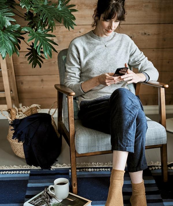 一位女士坐在配有灰色软垫的木材框架扶手椅上浏览移动设备,椅子下方是蓝色地毯。