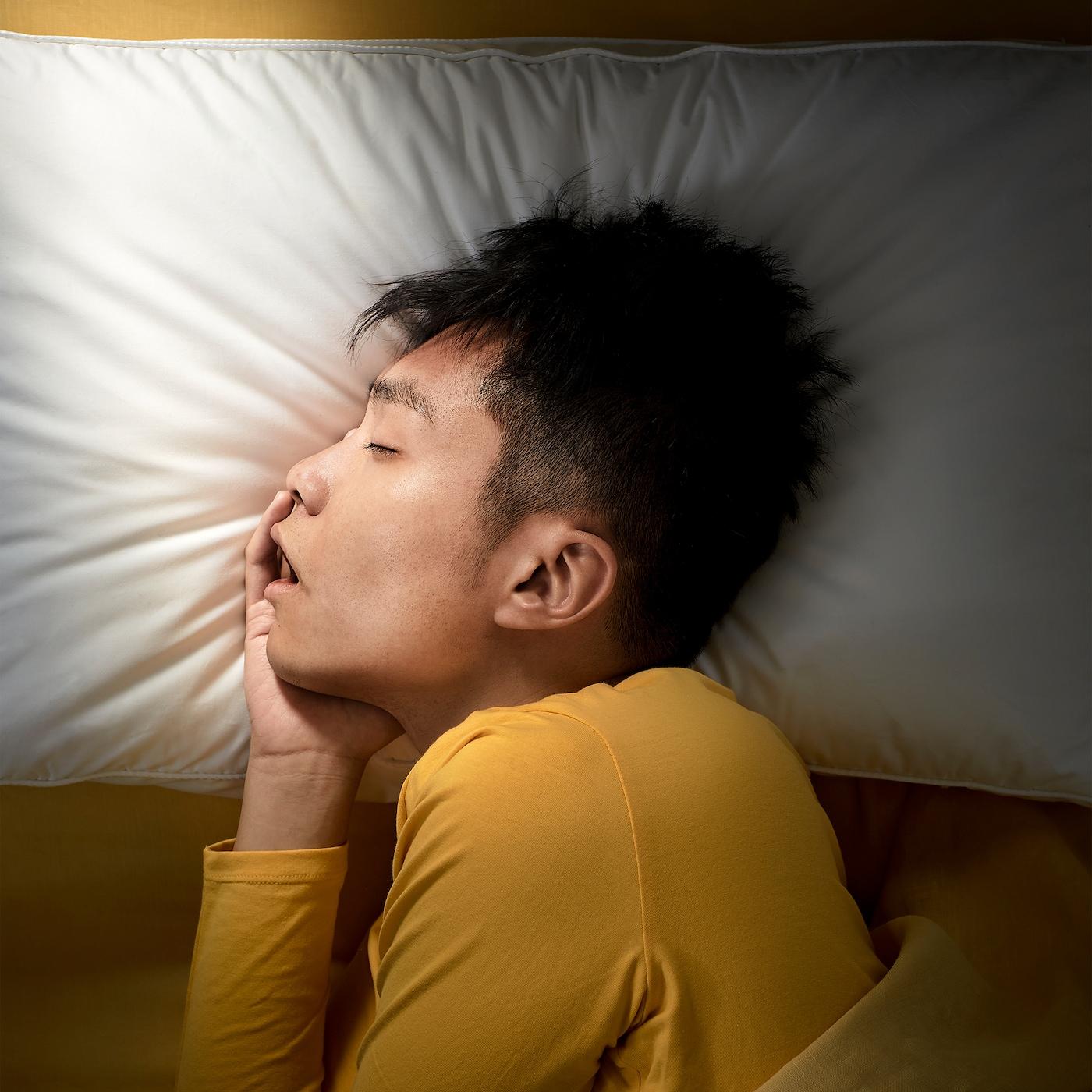 一位青年侧躺着枕在宜家 PRAKTVÄDD 普拉科特维德 人体工学枕上,睡得很沉。