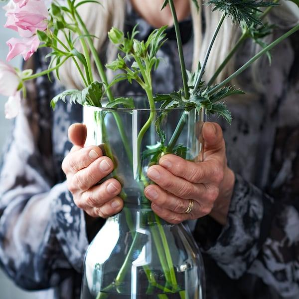 一位上了年纪的女士拿着 OMTÄNKSAM 沃姆安克萨姆 花瓶,花瓶里插着精心打造的植物。花瓶的造型易于提起搬动。