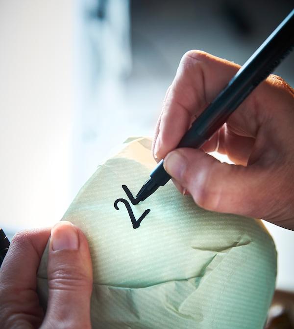一位设计师在每一个包装好的餐具上写上数字。