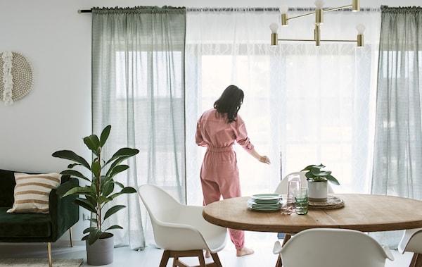 一位身穿粉色连体裤的女士给餐厅的法式窗户装窗帘。餐厅里摆着木餐桌和白色椅子。