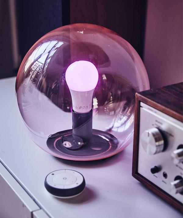 一盏圆形的粉色透明玻璃台灯,还有一个遥控器。