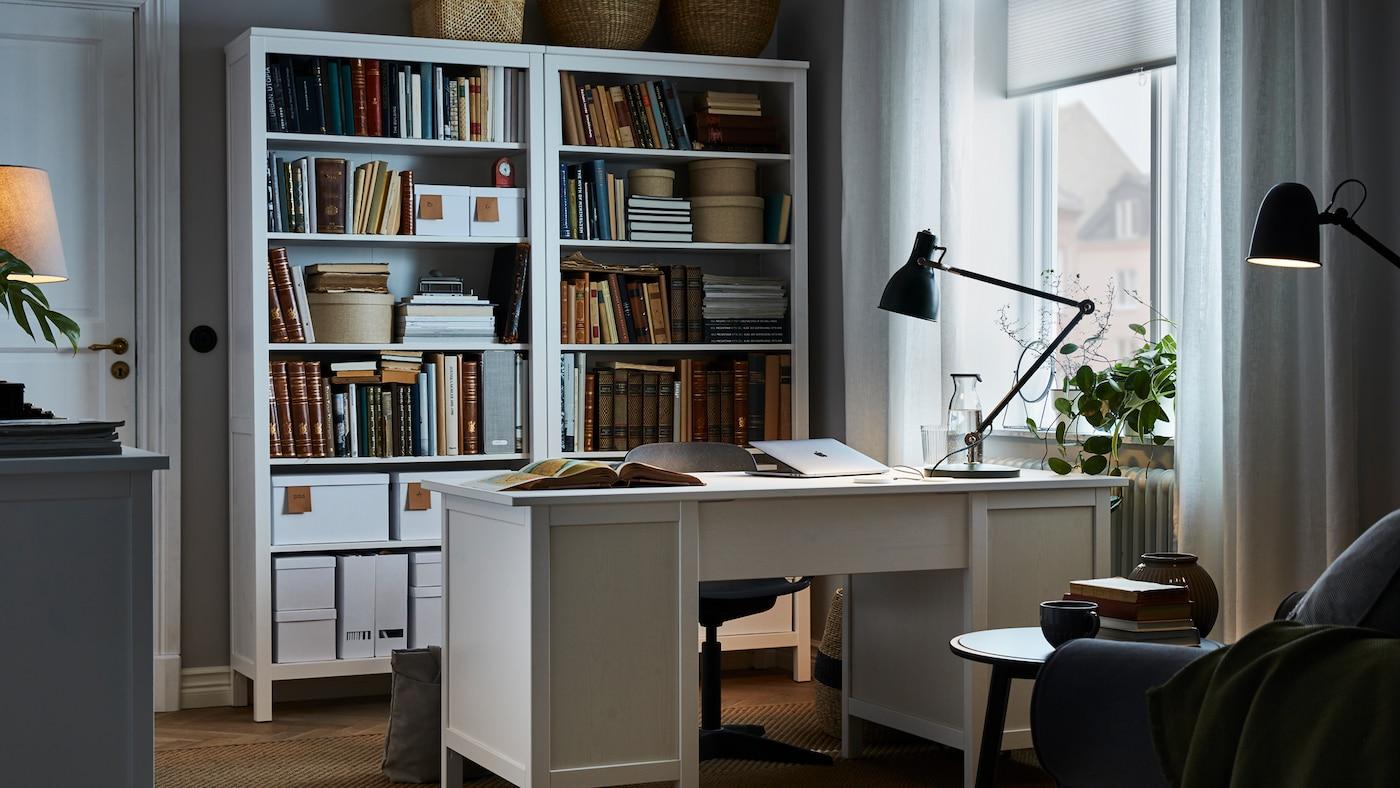 一张白色办公桌立于房间中央,桌面上放着一盏工作灯,办公桌背后还有一个与它配套的高书柜。