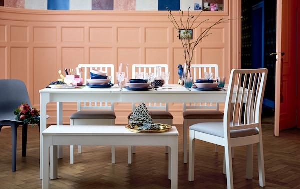 一张白色长餐桌、一条长凳和几把椅子,上面摆放着彩色餐具。