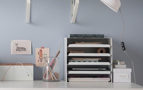 一张白色书桌,展示着清理书桌的物件,如用来装纸张和便笺簿的信盘、用于储物和整理线缆的储物盒以及装笔的玻璃花瓶