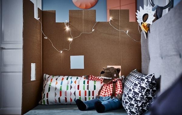 一张城堡形状的纸板固定在带靠垫的沙发一侧