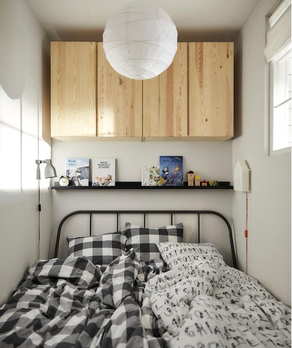 一张床上铺着两床羽绒被,上方的壁式图片架上摆着书,墙上装有木质橱柜。