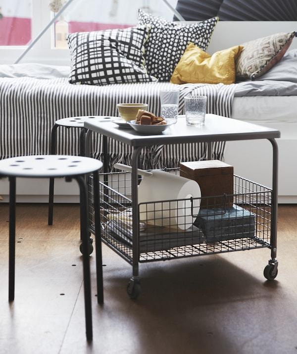 一张带轮子的桌子,下面有储物篮;两个小凳子和一张坐卧两用床。