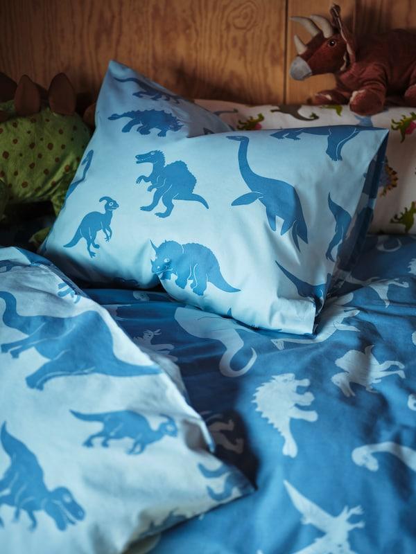 一张儿童床上铺着一套深浅相间的蓝色恐龙被子和枕头,两只JÄTTELIK 耶特里克恐龙 正偷偷向外张望。