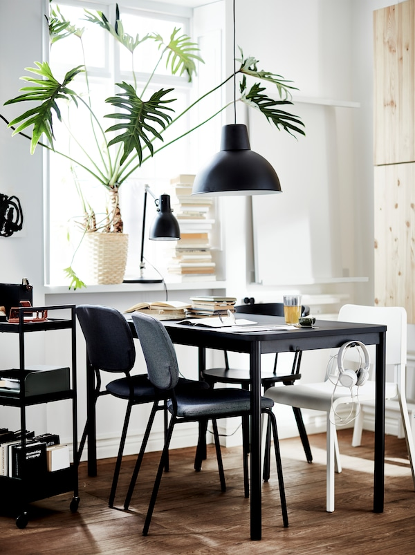 一张黑色的TOMMARYD 托玛瑞德 桌子,白色、灰色和黑色的四张不同椅子,黑色的灯具,窗台上有一棵大的植物。