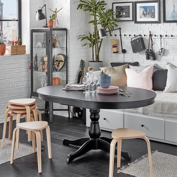 一张 INGATORP 英格托 黑色伸缩型餐桌展开着,桌子周围摆放着 KYRRE 叙勒 凳子,充当额外的座椅。