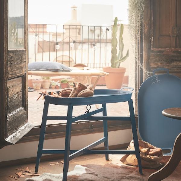 一张蓝色托盘桌摆在阳台木门前。