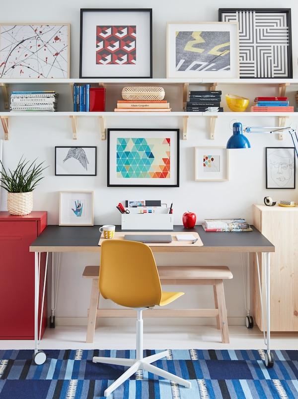 一张LEIFARNE 雷夫尼 转椅和LINNMON 利蒙/KRILLE 克瑞尔 带脚轮书桌,摆放在墙边,形成了一个工作区,四周为储物单元和艺术品。