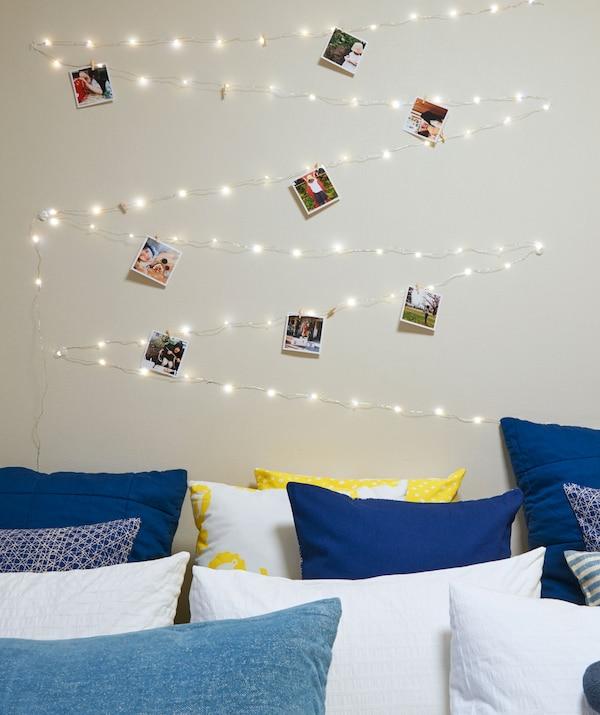 一张铺满靠垫的床,其上方挂着呈之字形的灯串和照片。