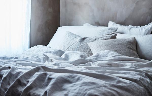 一张铺有灰色和白色床上用品的床。