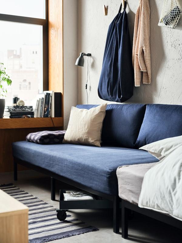 一张深蓝色的RÅVAROR 罗瓦露 坐卧两用床靠着混凝土纹的墙壁摆放。上方挂着一个RÅVAROR 罗瓦露 储物袋。