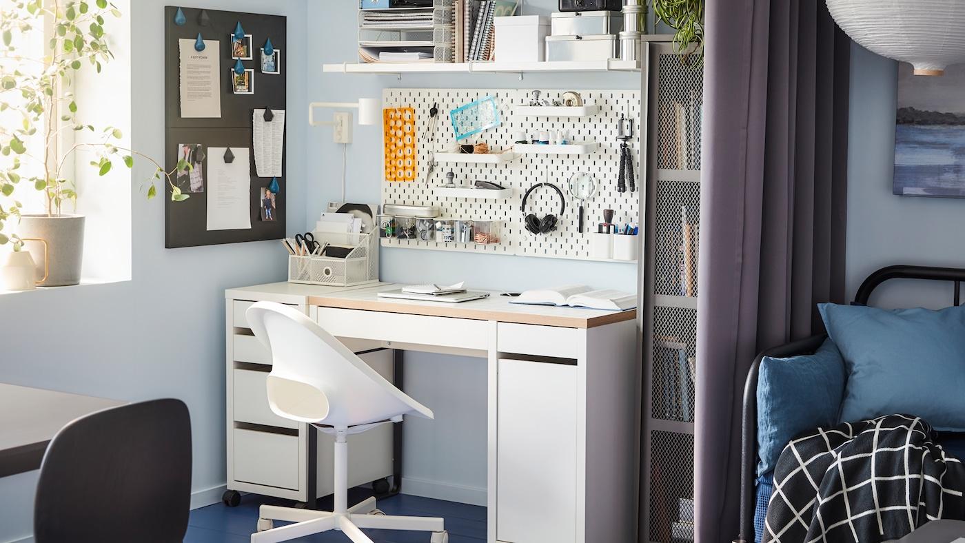 一张书桌、转椅和墙搁板,一块白色的小钉板,一个灰色的储物柜,旁边还有一个窗户。