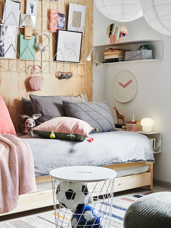 一张UTÅKER 于托克 叠床,上面摆满各种靠垫,床上方是一些纸质艺术品,旁边是BOTKYRKA 博西卡 搁架、储物柜和装饰品。