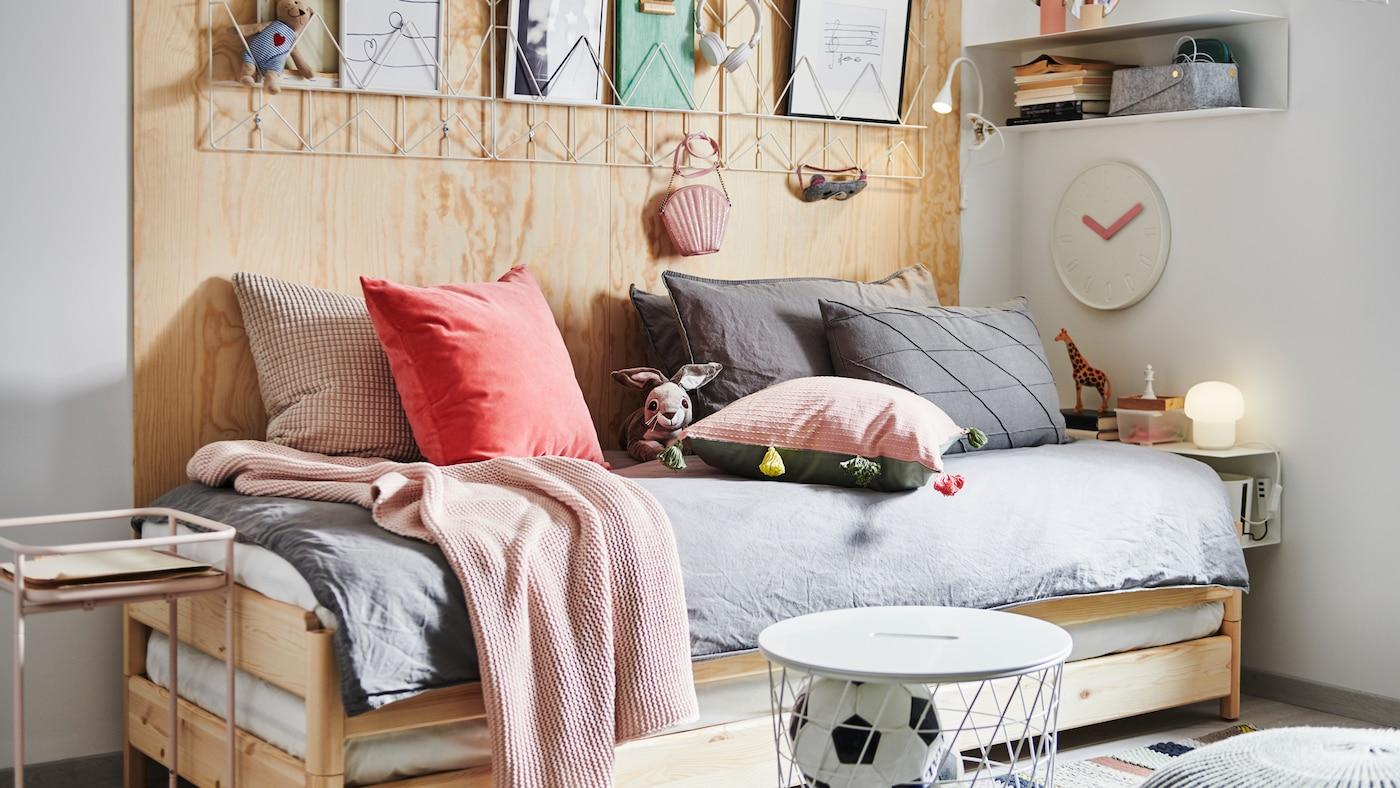 一张UTÅKER 于托克 叠床,上面摆满各种靠垫和纺织品,旁边是床边桌、储物柜和装饰品。