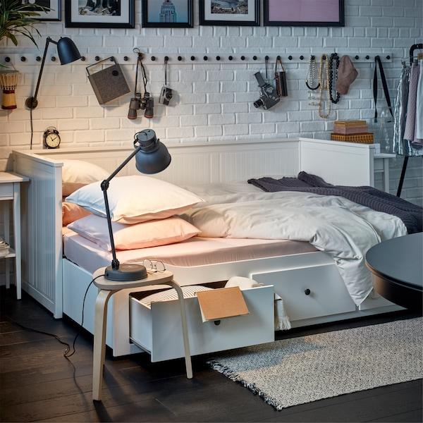 一张用来充当床的白色坐卧两用床,床上铺着舒适的床用纺织品,旁边放有一张凳子,凳子上放有台灯。