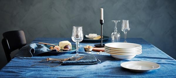 一张优雅的餐桌上铺着蓝色桌布,放着 KONUNGSLIG 克隆斯里格 酒杯、碟子、盘子、烛台和食物。