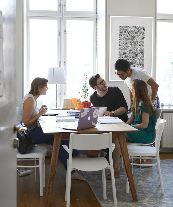 一张桌子上放着电脑和笔记本,人们聚集在周围。