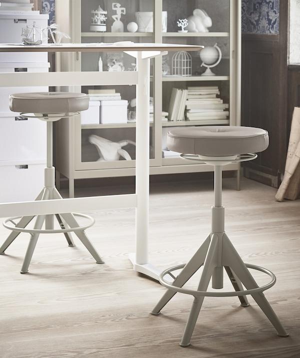 一张坐/站两用书桌和两把米色凳子,背后摆放着一个展示柜。