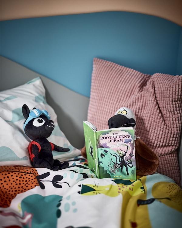 一只戴着蓝色护目镜的毛绒玩具猫,一只毛绒玩具猫头鹰,坐在床上阅读一本名为《The Root Queen's Dream》的书。