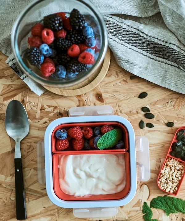 一只配有橙色分格的午餐盒,一个分格里装有酸奶,另一个分格里装有莓果。旁边还有一只装有夏莓的圆形玻璃罐。