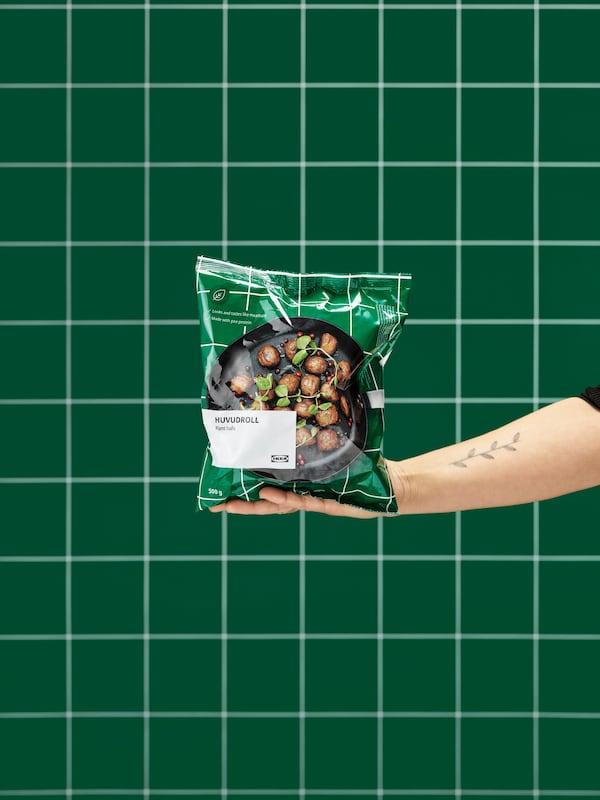 一只伸出的手中拿着一袋未开封的HUVUDROLL 胡福多 植物蛋白素肉丸。背景是绿色的瓷砖墙。