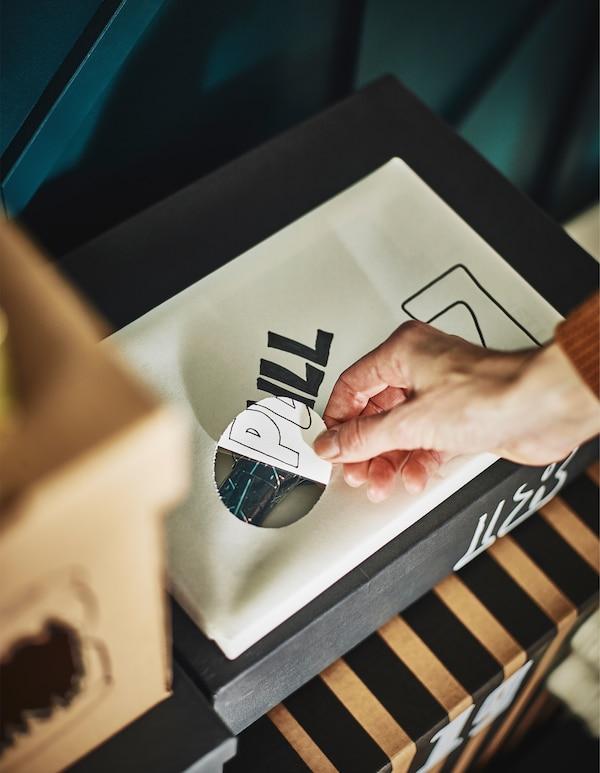 一只手抽出一张覆盖着包装盒孔洞的纸。