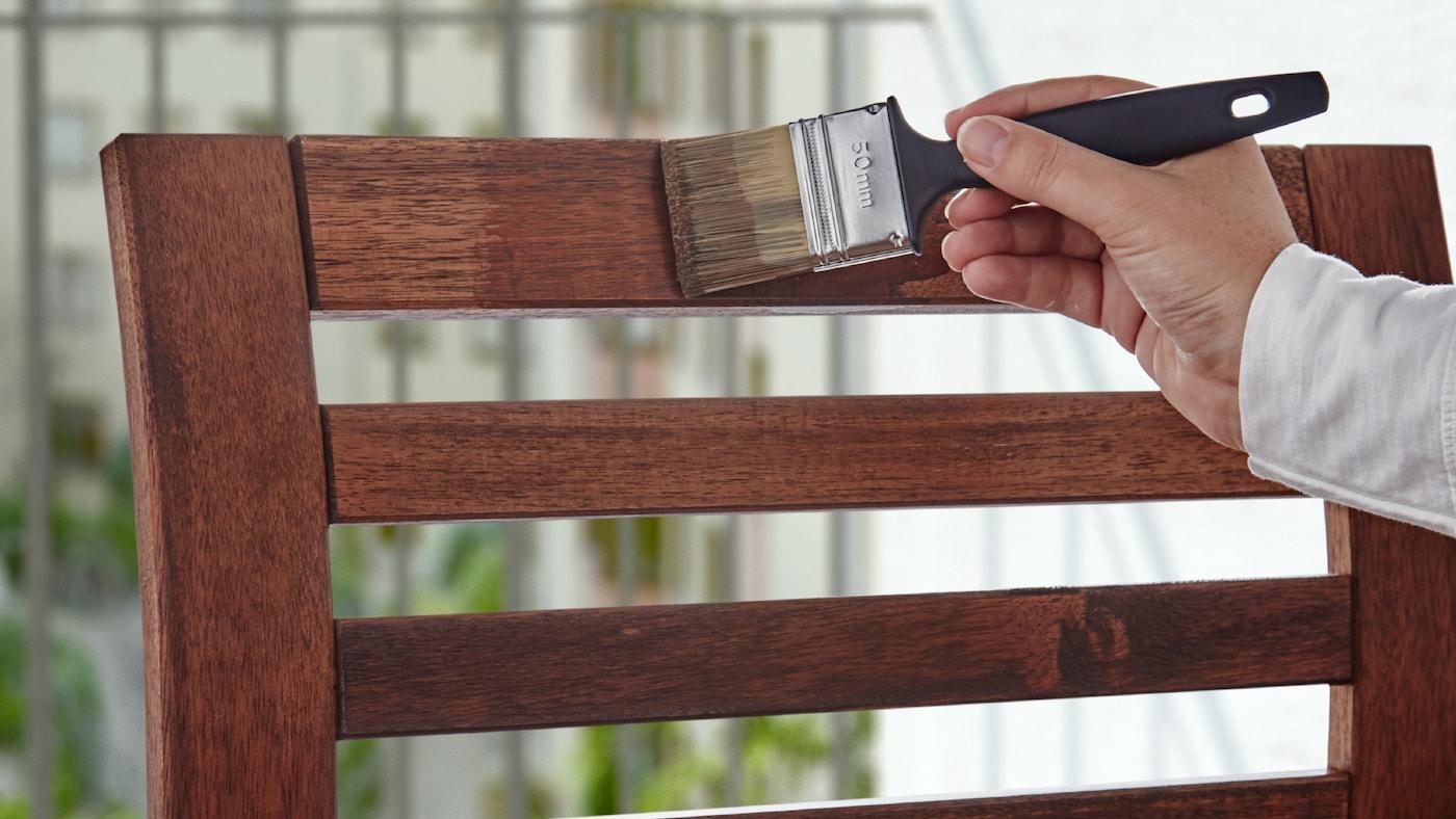 一只手拿着一把油漆刷,正在给一张木制户外椅子的椅背上漆。