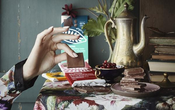 一只手正拿着一块巧克力,桌上摆放着巧克力排、书和水果。