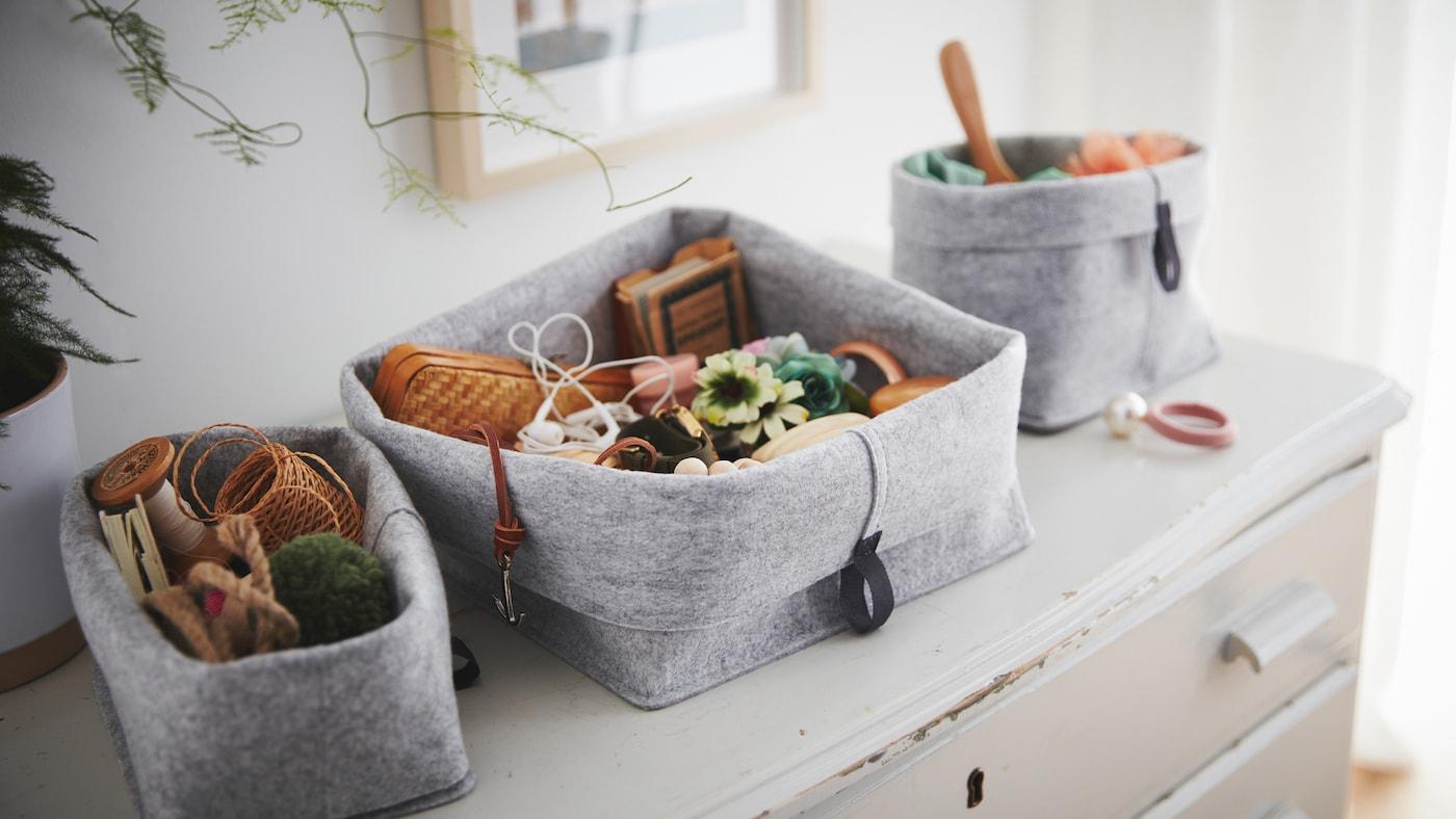 一组RAGGISAR 拉吉萨 布料篮子摆放在一张陈旧的抽屉柜上,里面装满了小饰品和杂物。