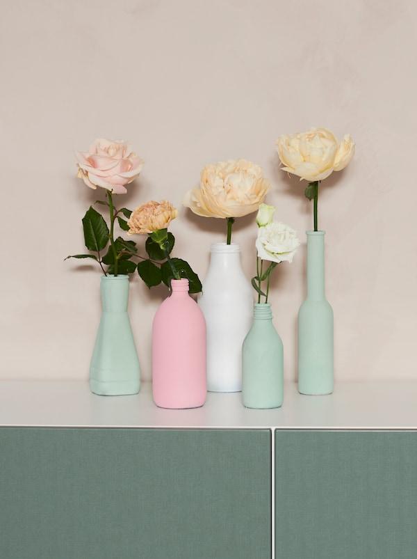 一组形状各异的旧瓶子被涂上淡彩色颜料,制成花瓶。每个花瓶里都插着一支 SMYCKA 思米加 装饰花支。