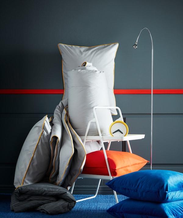 宜家 KUNGSBLOMMA 昆布鲁玛 灰色被套和枕套配换色饰边,旁边有闹钟、阅读灯、橙色和蓝色的枕头。
