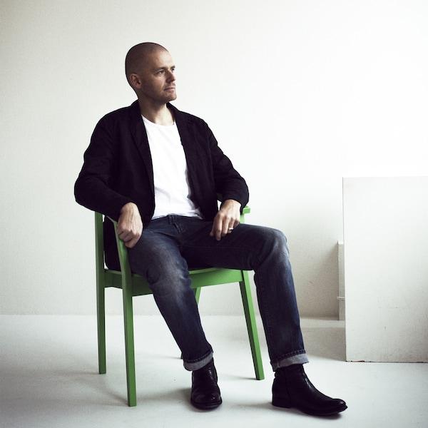 宜家设计师Ola Wihlborg坐在绿色椅子上的照片