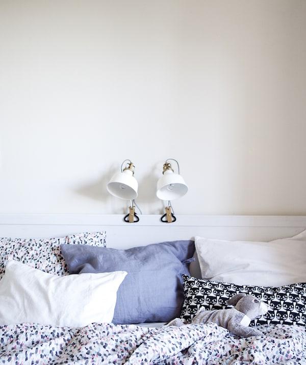 以白色为主色调的卧室里,床架上夹着两盏灯具。