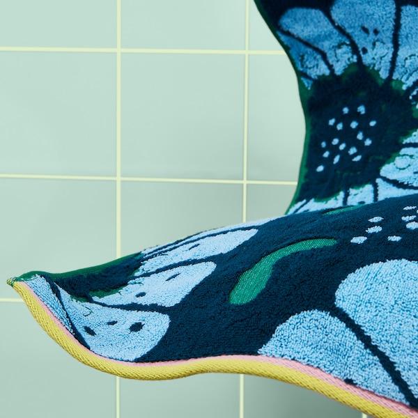 以深蓝色和绿色为背景颜色的宜家 SANDVILAN 桑德维兰 浴巾上印有提花编织的浅蓝色大型花卉图案。这款100%棉制浴巾的短边饰有粉色和黄色滚边。