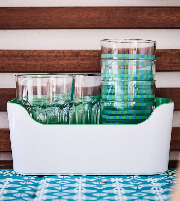 饮水玻璃杯堆叠摆放在桌面顶部开放式的塑料器具里。