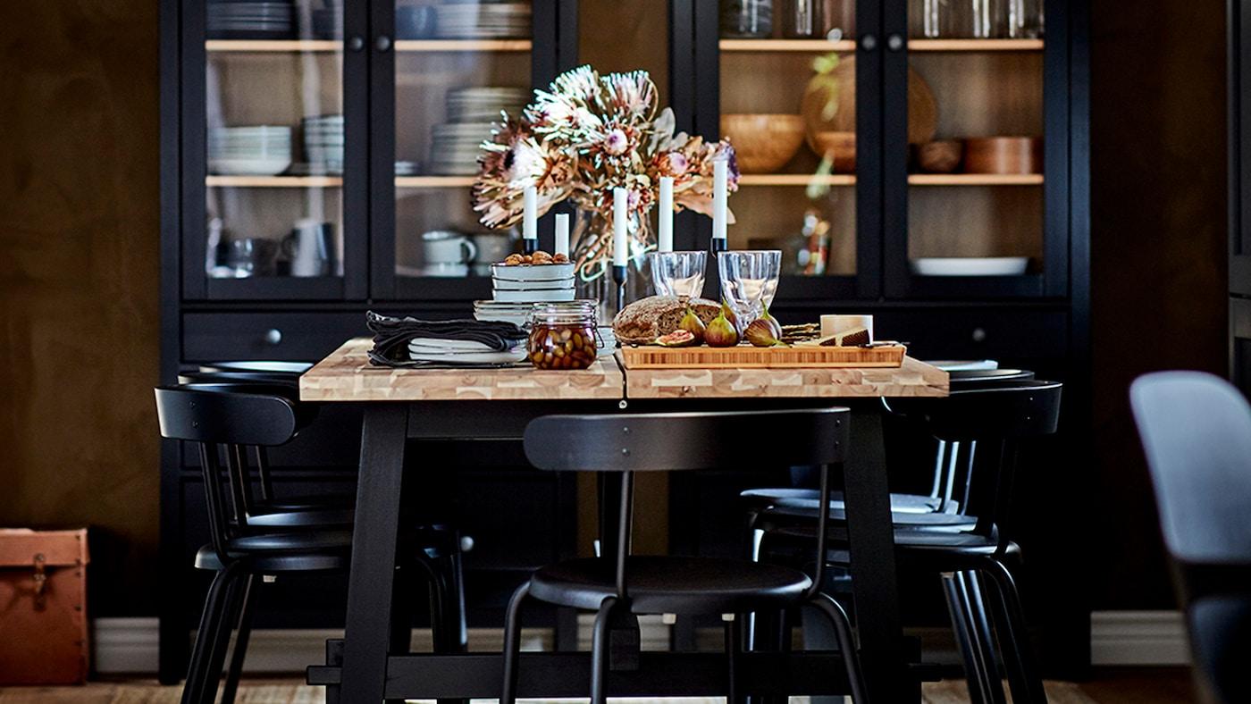 用餐区放着一张餐桌,带木质台面、黑色桌腿和黑色餐椅,后方是玻璃门柜。