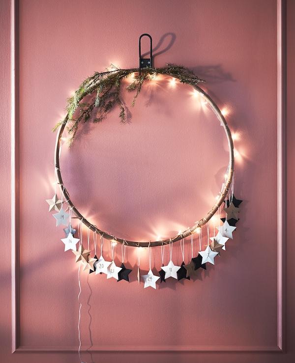 用灯、绿色植物和纸星星装饰的呼拉圈挂在墙壁上。