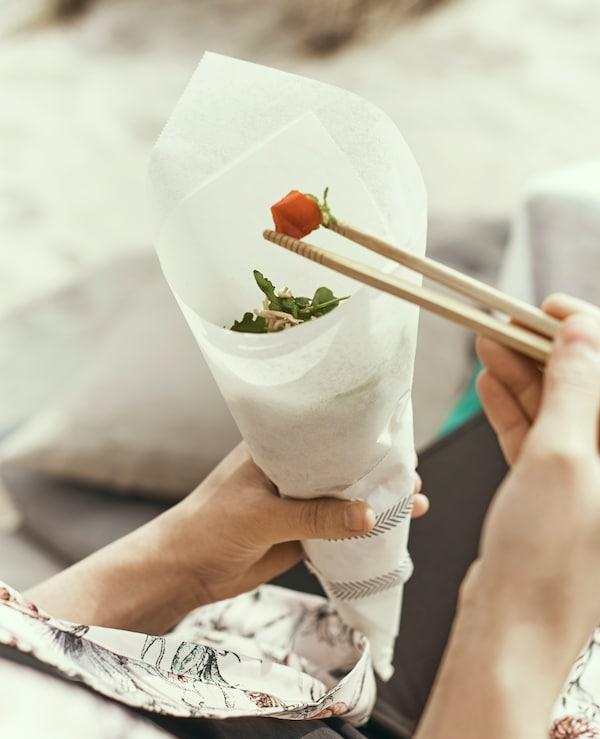 用筷子吃羊皮纸锥里的面条。